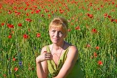 Porträt der Frau der durchschnittlichen Jahre auf einem Mohnblumengebiet Stockbild