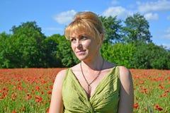 Porträt der Frau der durchschnittlichen Jahre auf einem Mohnblumengebiet Lizenzfreies Stockfoto