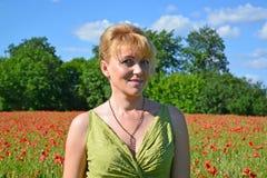 Porträt der Frau der durchschnittlichen Jahre auf einem Mohnblumengebiet Stockfotos