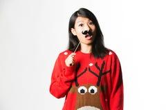 Porträt der Frau in der Weihnachtsstrickjacke, die mit dem gefälschten Schnurrbart steht lizenzfreies stockfoto