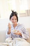 Porträt der Frau, die Getreide auf Sofa isst Stockbild