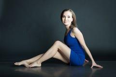 Porträt der Frau im blauen kurzen Kleid, das auf dem Boden auf dunklem Hintergrund sitzt Lizenzfreie Stockfotografie