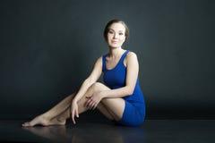 Porträt der Frau im blauen kurzen Kleid, das auf dem Boden auf dunklem Hintergrund sitzt Lizenzfreies Stockfoto