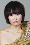 Porträt der Frau im goldenen Kostüm über grauem Hintergrund Lizenzfreies Stockfoto