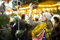 Porträt der Frau im Mantel, der an Weihnachtsmesse am Abend aufwirft Lizenzfreies Stockfoto