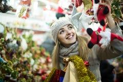 Porträt der Frau im Mantel, der an Weihnachtsmesse am Abend aufwirft Stockfotografie