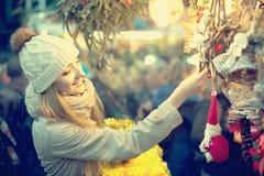 Porträt der Frau im Mantel, der an Weihnachtsmesse am Abend aufwirft Stockfotos