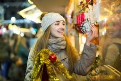 Porträt der Frau im Mantel, der an Weihnachtsmesse am Abend aufwirft Lizenzfreie Stockbilder