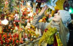 Porträt der Frau im Mantel, der an Weihnachtsmesse am Abend aufwirft Stockbild