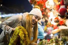 Porträt der Frau im Mantel, der an Weihnachtsmesse am Abend aufwirft Stockbilder