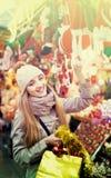 Porträt der Frau im Mantel, der an Weihnachtsmesse am Abend aufwirft Lizenzfreie Stockfotografie