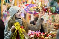 Porträt der Frau im Mantel, der an Weihnachtsmesse am Abend aufwirft Lizenzfreie Stockfotos