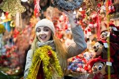 Porträt der Frau im Mantel, der an Weihnachtsmesse am Abend aufwirft Stockfoto