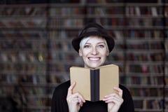 Porträt der Frau im schwarzen Hut mit geöffnetem Buch lächelnd in einer Bibliothek, blondes Haar Hippie-Studentenmädchen Lizenzfreie Stockbilder