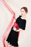 Porträt der Frau im schwarzen Kleid mit rotem Gurt Stockbilder