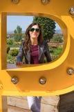 Porträt der Frau innerhalb des gelben großen Metallbuchstaben Lizenzfreie Stockbilder