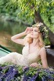 Porträt der Frau mit dem Kranz, der im Boot mit Blumen sitzt Sommer Lizenzfreie Stockfotos