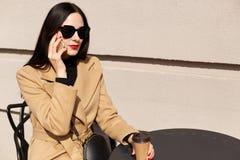 Porträt der Frau mit dem langen dunklen Haar, tragendem modernem beige Mantel und trinkendem Mitnehmerkaffee, Rest Café habend im stockfotos