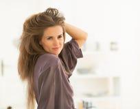 Porträt der Frau mit dem langen Haar, das im Spiegel schaut stockbild