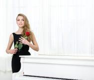 Porträt der Frau mit der Rotrose, die nahe dem Klavier steht Lizenzfreies Stockfoto