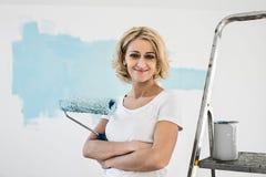 Porträt der Frau mit Farbenrolle im neuen Haus Stockbilder