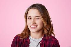 Porträt der Frau mit fröhlichem Ausdruck, Blinzeln mustern, wie Flirts mit gutaussehendem Mann, ihre Sympathie ausdrückt, gekleid Lizenzfreies Stockfoto