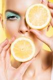Porträt der Frau mit Scheiben der Zitrone nahe Gesicht Lizenzfreies Stockbild