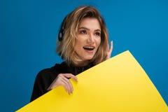 Porträt der Frau positiv lächelnd und Kopfhörer tragend Gelbe Pappe zeigte für annoncieren an stockfotos
