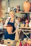 Porträt der frohen Frauentonwarenarbeitskraft mit keramischer Tonware lizenzfreie stockfotos