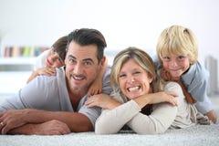 Porträt der frohen glücklichen Familie, die auf Teppichboden liegt Lizenzfreie Stockfotografie