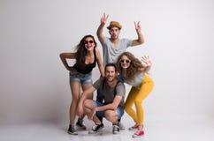 Porträt der frohen jungen Gruppe Freunde mit dem Hut und Sonnenbrille, die in einem Studio stehen lizenzfreie stockfotos