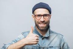 Porträt der frohen Mitte alterte männliches witth starken Bart und Schnurrbart zeigt seine Zufriedenheit mit etwas, anhebt Daumen lizenzfreies stockfoto
