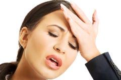 Porträt der Geschäftsfrau, die enorme Kopfschmerzen hat stockbild