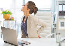 Porträt der Geschäftsfrau mit Rückenschmerzen Lizenzfreie Stockfotos
