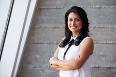 Porträt der Geschäftsfrau Standing Against Wall im Büro Stockfoto