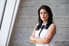 Porträt der Geschäftsfrau Standing Against Wall im Büro Stockfotos