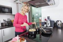 Porträt der glücklichen älteren Frau, die Lebensmittel an der Küchenarbeitsplatte kocht Stockfotos