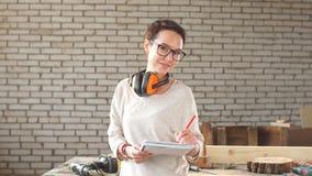 Porträt der glücklichen attraktiven fleißigen Berufsarbeitnehmerin mit Stift und der Tablette in der Werkstatt stock footage