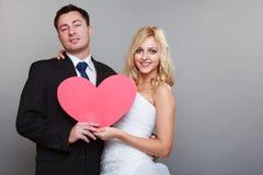 Porträt der glücklichen Braut und des Bräutigams mit rotem Herzen auf Grau Lizenzfreie Stockfotografie