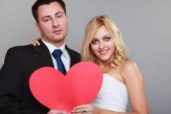 Porträt der glücklichen Braut und des Bräutigams mit rotem Herzen auf Grau Lizenzfreies Stockfoto