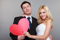 Porträt der glücklichen Braut und des Bräutigams mit rotem Herzen auf Grau Stockfotos