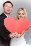 Porträt der glücklichen Braut und des Bräutigams mit rotem Herzen auf Grau Stockfoto