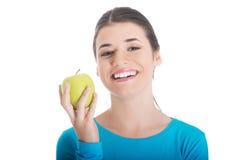 Porträt der glücklichen Brunettefrau, die einen Apfel hält Lizenzfreie Stockbilder