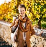 Porträt der glücklichen eleganten Brunettefrau im Herbstpark stockfoto