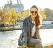 Porträt der glücklichen eleganten Frau, die auf dem Geländer n Paris sitzt stockfotografie