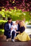 Porträt der glücklichen Familie auf dem Weg entlang der blühenden Frühlingsstraße lizenzfreie stockbilder