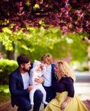 Porträt der glücklichen Familie auf dem Weg entlang der blühenden Frühlingsstraße lizenzfreies stockbild