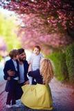 Porträt der glücklichen Familie auf dem Weg entlang der blühenden Frühlingsstraße stockfotografie