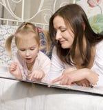 Porträt der glücklichen Familie, der Mutter und der Tochter im Bettlesebuch Lizenzfreies Stockfoto