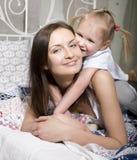 Porträt der glücklichen Familie, der Mutter und der Tochter im Bettlesebuch Lizenzfreies Stockbild
